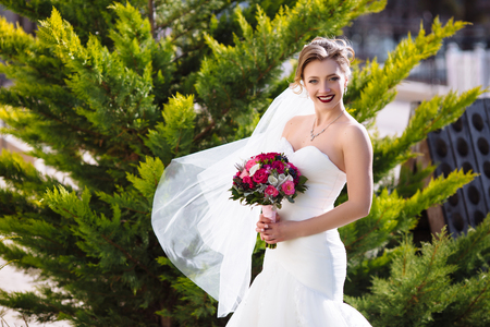 A slender bride in a tight wedding dress is standing in the garden on the background of trees. A gust of wind blows her dress and cotton wool, the girl cheerfully smiles and enjoys the moment. Stock Photo