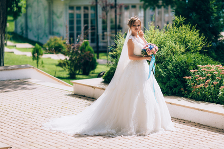 Beautiful bride in a white dress posing outdoors in a park. The girls bouquet is rewritten with blue ribbons. Stock Photo