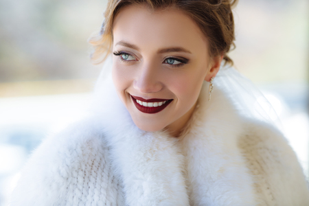 A close view of the face of a young girl with a scarlet lip color. The model is smiling broadly and showing white teeth, staring into the distance with blue eyes. Close-up portrait.