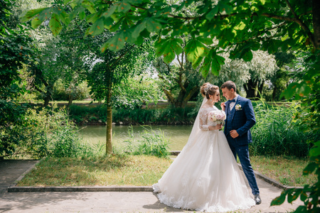 Newlyweds are walking among the green trees in the park. The bride in a snow-white lush dress and with a gently pink bouquet of pions hugs her fianc in a stylish suit. Stock fotó - 103044458