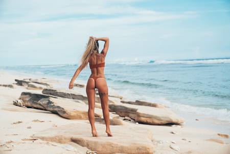 The concept of freedom, freshness, travel. View from the back of a young female model walking along an empty beach dressed in a stylish outdoor swimsuit.