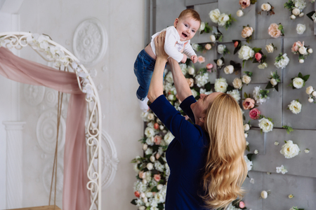The woman lifted her little child up in her arms and is spinning, the baby is having fun and laughing. They are in a beautiful room decorated with flowers.