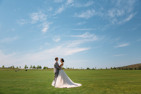 newlyweds are walking along the green field of the golf club on a wedding day. The groom in a business suit is gray and the bride in a luxury white dress with a veil are holding hands.