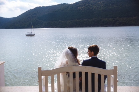 A man in a stylish expensive suit is sitting on a bench with his fianc e in a veil and a white dress, admiring the wide river along which ships and yachts swim.