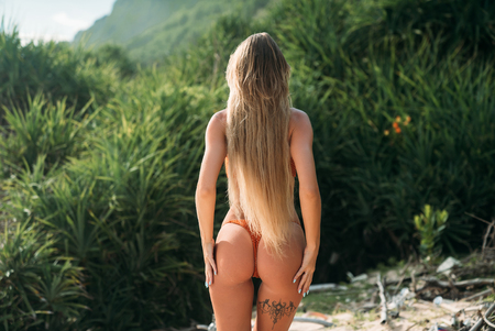 The view from the back is a sexy girl with white long hair that touch the priests standing in a bikini and put her hands on her hips. Beautiful round ass model on the beach.