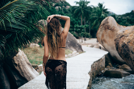 rear view of a sexy girl with a round ass walks along the alley along the sea water and stones, corrects the hair with her hand, wears a swimsuit and a transparent pareo through which you can see her ass.
