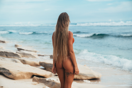 View from the back of the model with a tanned smooth skin stands on the seashore in a bikini and admires the waves coming to her feet. The concept of summer mood, rest, relaxation, travel.