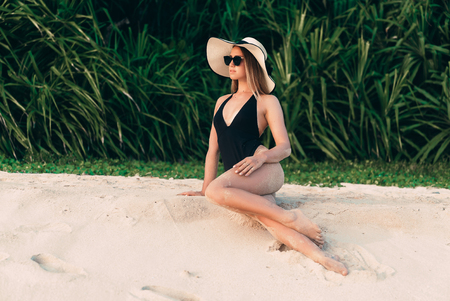 A young European woman came to rest on her villa near the sea, sunbathing on white sand near the water, wearing an expensive hat, a swimsuit and sunglasses.