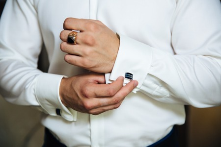 A man in a business suit, white shirt close-up of a cropped frame. The businessman puts on cufflinks, wears a gold finger ring on his finger, an expensive leather belt. Stock Photo