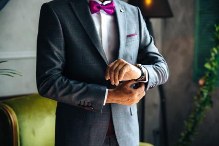 El plan rudo es un cuerpo recortado de un elegante hombre de negocios que se casa hoy, se pone un traje de moda, viste una camisa blanca y elegantes relojes de cuero caros, se abrocha los gemelos en la manga.