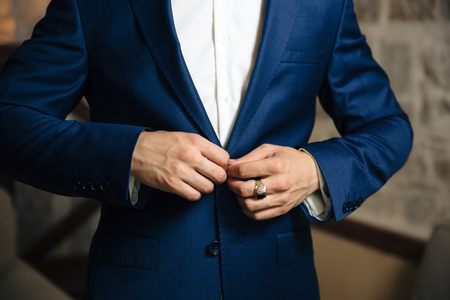 Close-up of a cropped frame of a business stylish man buttoning his jacket, standing in a stylish office with designer repair. Stockfoto