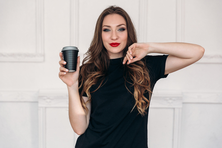 A beautiful, cheerful, radiant young girl wears everyday stylish clothes, paints her lips with red lipstick, and believes that you need to start the day with coffee.