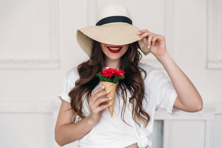Young beautiful woman vegan portrait, wearing a straw hat with large fields and covering her eyes, lips red. The girl thinks that sweets are harmful to the figure, so she has red flowers in the horn.