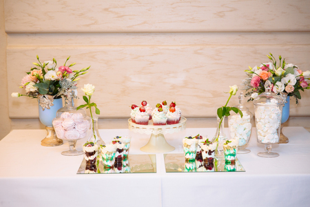 Candy bar, a table with sweets and desserts on the table. Buffet with delicious cupcakes, cake pops, biscuits, flowers.