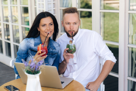 A man and a woman sat down to relax in a cafe, drinking cocktails through straws. A man is working behind his laptop. The concept of people, freelancers, gadgets, technology.