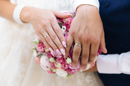 Close-up of the hands of the newlyweds with wedding rings, gently touch the wedding bouquet of peonies. Imagens