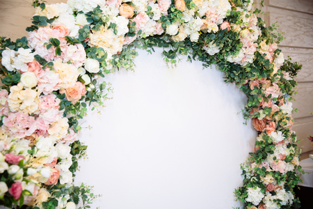 The concept of wedding decor, street decoration, wedding arch is decorated with flowers - pink and white peonies. Wedding day, ceremony place for the bride and groom, decor, flowers, florists. 스톡 콘텐츠