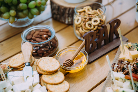 Close-up cheese bar of several kinds of cheese, snacks, honey, nuts decorated on wooden table at the wedding party. Concept of food. 스톡 콘텐츠