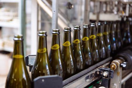 Bottiglie di vetro sulla linea di trasporto automatica presso la fabbrica di champagne o vino. Impianto per l'imbottigliamento di bevande alcoliche.