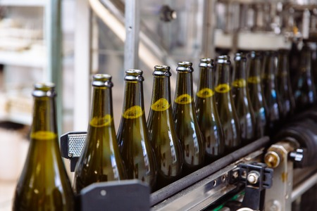 Butelki szklane na automatycznej linii transportowej w fabryce szampana lub wina. Zakład rozlewu napojów alkoholowych.