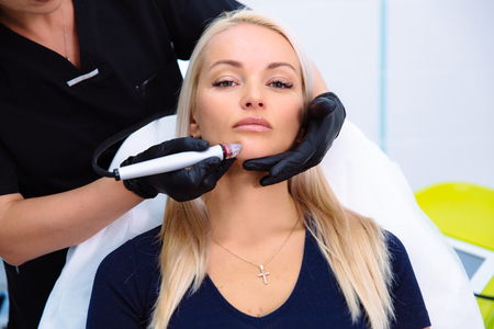 Close-up women face and cosmetologist hand carries out procedures on the patients face with a hydro-peeling apparatus.