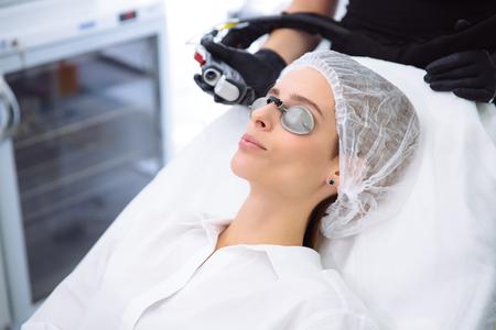 Il cosmetologo ravvicinato effettua un trattamento laser sul viso di una giovane donna, procedure di epilazione per la depilazione presso la clinica di bellezza SPA. Archivio Fotografico