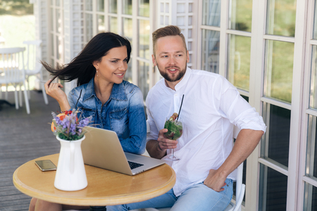 Attractive young guys sit at a table on the terrace in a cafe, enjoy drinks, talk on fun topics. A guy freelancer took a laptop with him, because he can not be distracted for a long time from work.