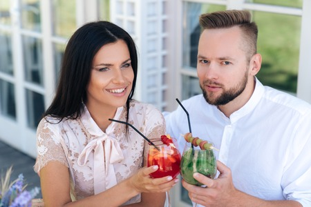 Close-up, cropped frame, an attractive brutal man, has a European appearance, a stylish haircut and a beard brought his smiling beautiful girl to a European in a cafe, treats a cocktail.