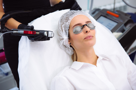 Close-up cosmetologist makes a laser treatment to young woman face, hair removal epilation procedures at beauty SPA clinic. Stock Photo
