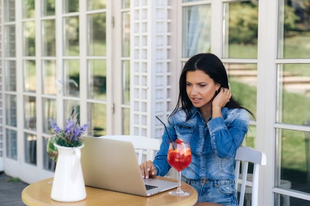 A beautiful freelancer girl received some unwanted email to her inbox on the Internet. A woman is unhappy with the message she is reading, she thinks how to respond.