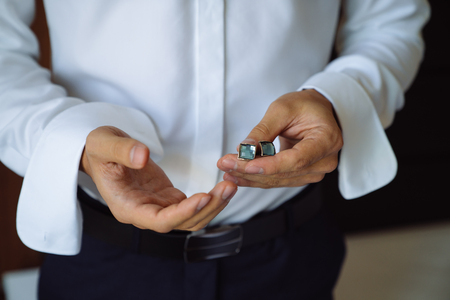 Closeup businessman hands with cufflinks. Man in a business suit, white shirt. Preparing the groom on the wedding day Stock Photo