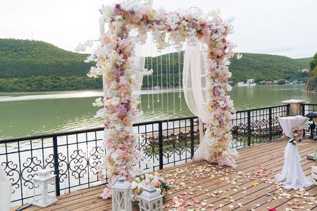 Día de la boda, lugar de ceremonia para los novios, decoración, flores. Concepto de decoración, el arco de la boda está decorado con flores: peonías rosas y blancas.