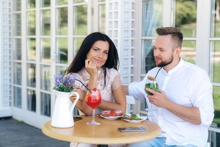 Man and a woman are sitting in a cafe, looking at each other lovingly, eating delicious desserts and drinking cocktails. A man wants to make an offer today to marry a beautiful girl. Stockfoto