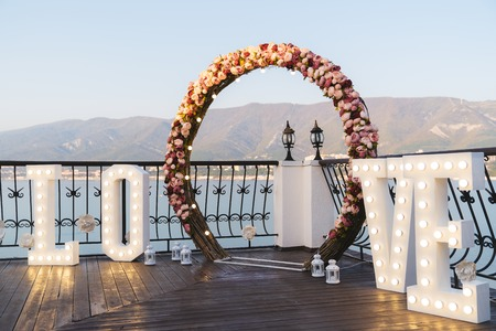Wedding arch decorated with big letters love and lamps, ceremony place for the bride and groom, decor, flowers pink and white roses. Banco de Imagens - 112015736