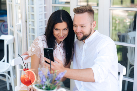Close-up of beautiful young people sitting in a cafe, taking a photo on the phone. A man makes a selfie with his happy bride. The girl and the guy have a European appearance Stock fotó