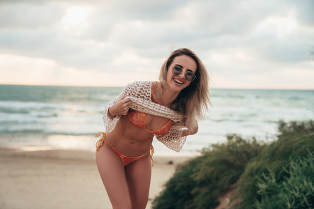 Good-loking model in brown swimsuit and sunglasses laughing and posing at sunset on the sandy beach