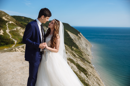 Beautiful couple of newlywed hugging at wedding day on cliff with ocean view Banco de Imagens - 114412231