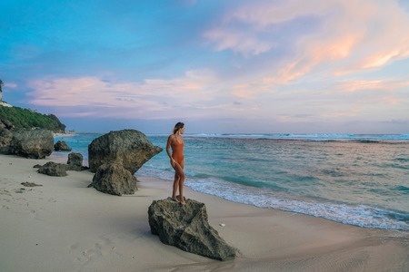 Slim girl in swimsuit standing on big stone at wild beach background of beautiful sunset