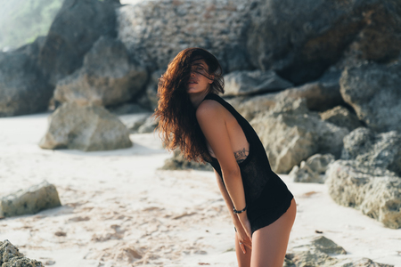 Portrait of sexy brunette model in knitted sweater posing on the sandy beach, big stones and rock on background.