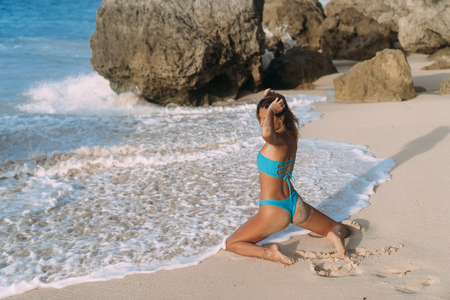 Slim girl with sexy buttocks in bright blue swimsuit posing in waves of ocean on sandy beach