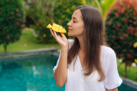 Portrait of attractive girl holds slice of mango in her hand, sniffs it and going to eat
