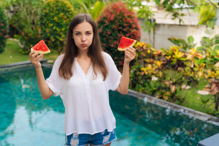 Portrait girl holds two slices of watermelon in her hands and makes funny face inflates her cheeks