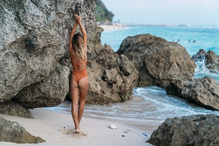 Backside view sexy girl in swimsuit with raised arms standing near rock on ocean beach Фото со стока