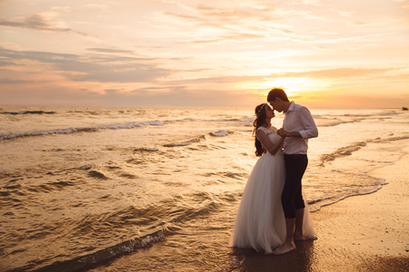 Bride and groom hugging and hold each others hands at beautiful sunset background. Newlyweds at wedding day on ocean beach Stock fotó