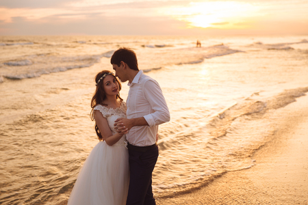 Happy bride and groom hugging on ocean beach at sunset time. Romantic couple newlyweds on their wedding day. Banco de Imagens - 116767385