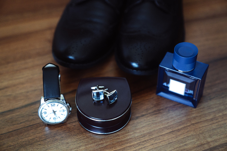 Mens leather shoes, watches and cufflinks on the background of a brown table. Clothing accessories businessman. Concept of grooms accessories at wedding day.