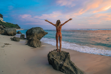 Backside veiw slender girl in swimwear with wide open arms stands on beach, looks at ocean and beautiful sunset