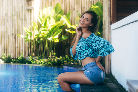 Happy sexy girl in denim shorts and top sits on pool. Young tanned model resting on summer day