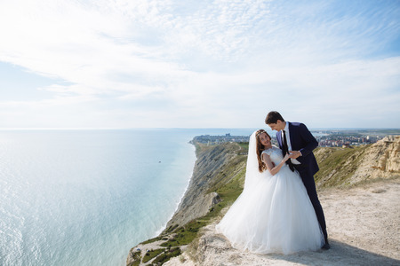 Beautiful couple of newlywed hugging at wedding day on cliff with ocean view Banco de Imagens - 117836997