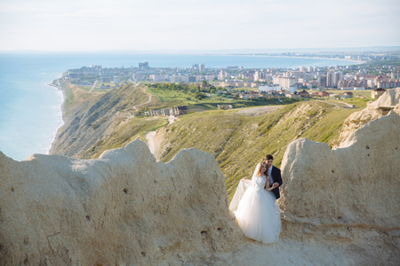 Beautiful couple of newlywed hugging at wedding day on cliff with ocean view